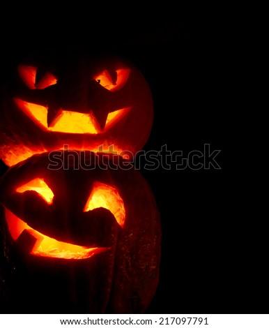 Illuminated cute halloween pumpkins isolated on black background - stock photo