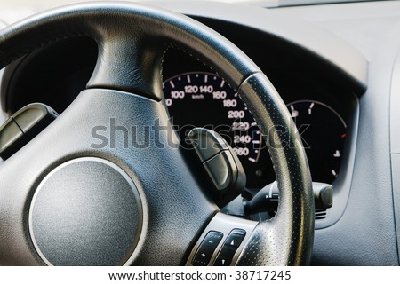 Illuminated dashboard and steering wheel of a modern car - stock photo