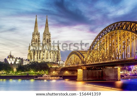 Illuminated Dom in Cologne with bridge and rhine at sunset - stock photo