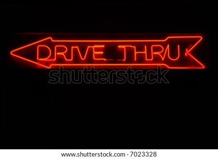 Illuminated drive thru neon sign with arrow pointing left - stock photo