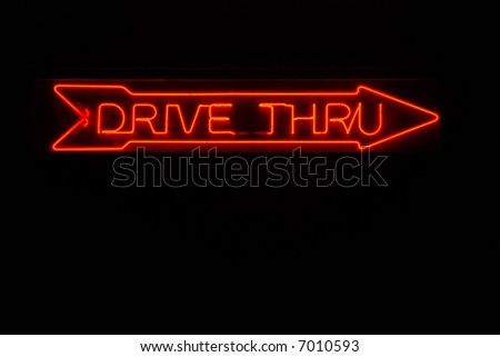 Illuminated drive thru neon sign with arrow pointing right - stock photo