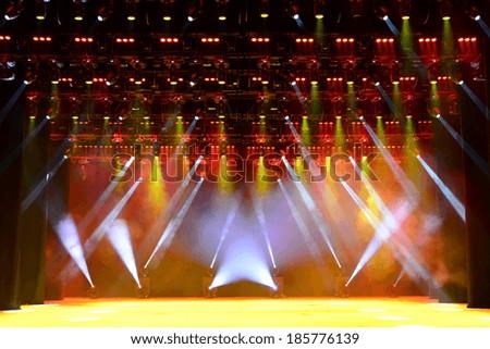 Illuminated empty concert stage with smoke - stock photo