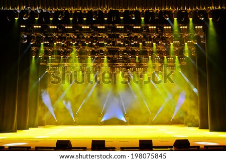 Illuminated empty concert stage with smoke and rays of light - stock photo