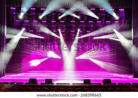 Illuminated empty theater stage with fog - stock photo