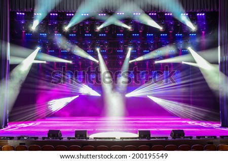 Illuminated empty theater stage with smoke and rays of light - stock photo