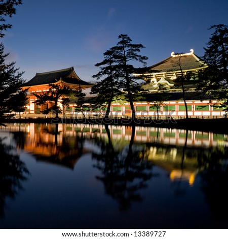 Illuminated evening view of the gate and wall surrounding Todai-ji temple with a pond in the foreground in Nara, Japan.  Todai-ji temple houses a huge bronze statue of Buddha