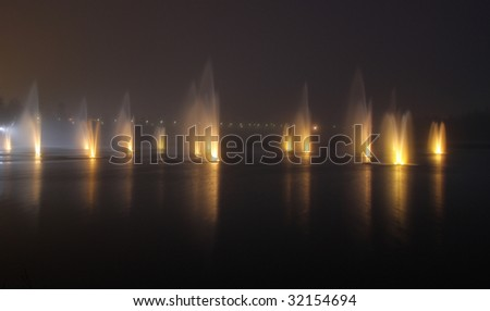 Illuminated fountains on a foggy night in Oulu, Finland - stock photo