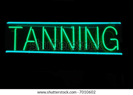 Illuminated green and blue tanning neon sign on black - stock photo