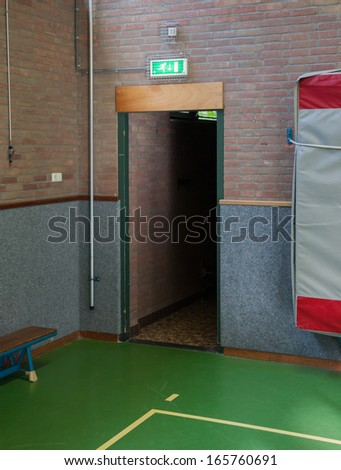Illuminated green emergency exit sign in an old school gym - stock photo