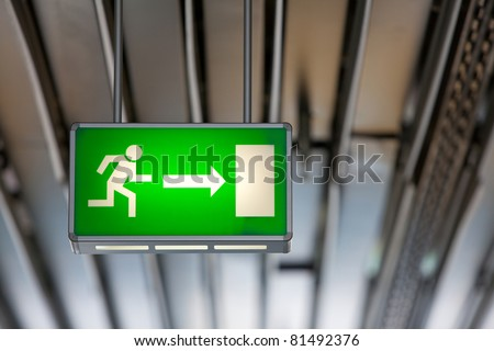 Illuminated green exit sign suspended from the ceiling in a public transportation facility. Signage consists of a human figure running and an arrow pointing at a door. - stock photo