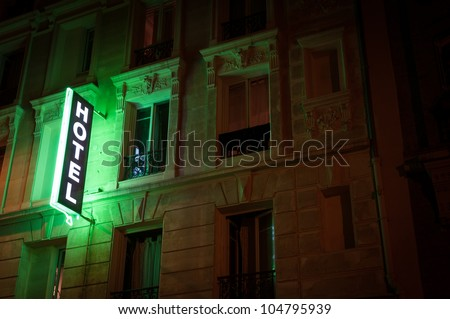 Illuminated green hotel sign on building. Paris, France, Europe.