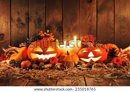 illuminated halloween pumpkins, candles, nuts, maize-cob and appleon straw in front of old weathered wooden board in candlelight - stock photo