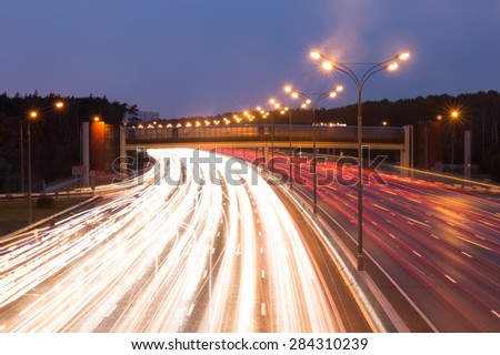 Illuminated highway at evening with light trails - stock photo