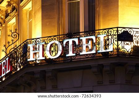 Illuminated hotel sign taken at dusk - stock photo