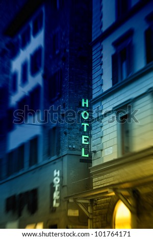 Illuminated hotel signs taken at dusk. Tilt shift lens and intentionally used two gradient glass filter to emphasize the HOTEL letters. Useful file for your site, brochure or flyer about hotel offers. - stock photo