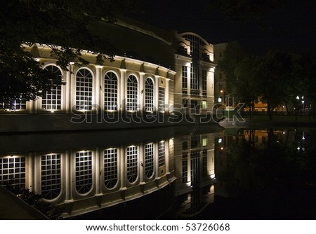 Illuminated house in the night and its reflection in the pond's water