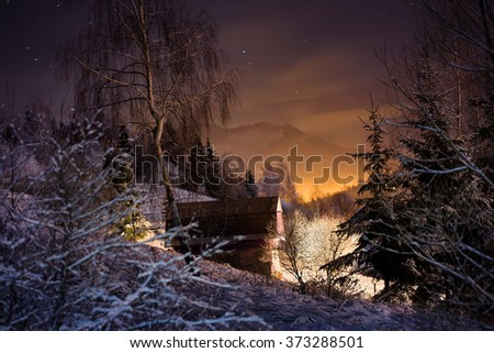 Illuminated house in winter forest in the mountains