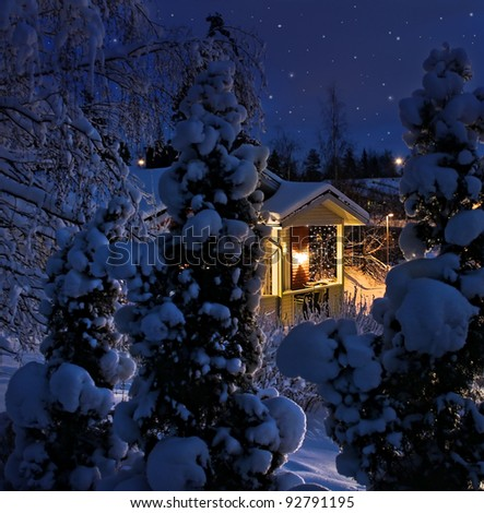 Illuminated house on snowy Christmas winter evening blue moment - stock photo