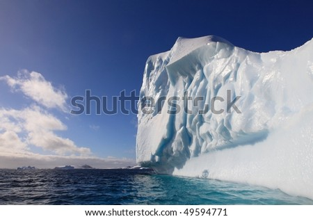 Illuminated Iceberg in Antarctica seen from a dinghy - stock photo