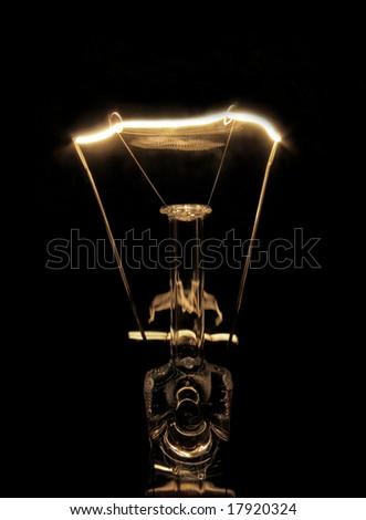 Illuminated light bulb glowing on a black background - stock photo