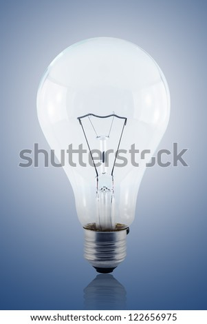 Illuminated light bulb on blue background including clipping path - stock photo