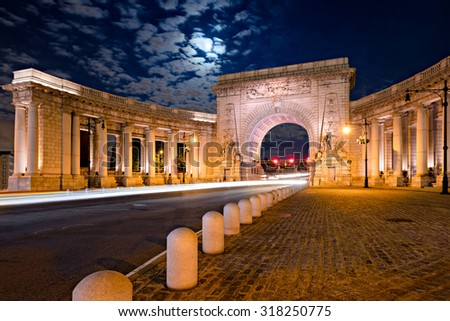 Illuminated Manhattan Bridge entrance with triumphal arch and colonnade on a moonlit night. New York City.