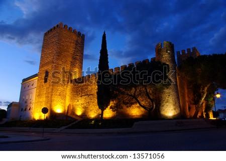 Illuminated medievel castle at dusk - stock photo