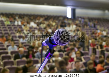 illuminated microphone on the stage and auditorium - stock photo