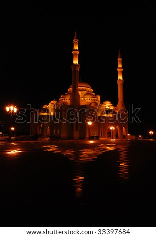 Illuminated mosque against black background - stock photo