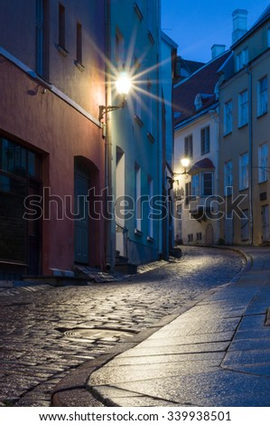 Illuminated narrow street at night in Tallinn Old Town, Estonia - stock photo