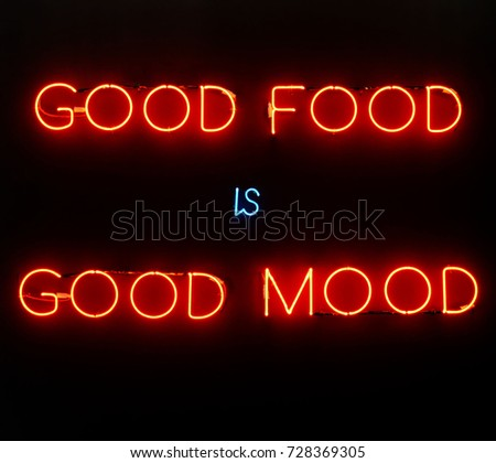 Illuminated neon sign showing good food is good mood on black background