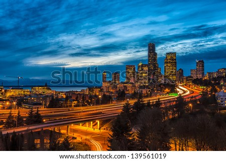 Illuminated night view of downtown Seattle and busy freeways in the foreground with the mountains and bay in the background. Dramatic night sky with clouds. - stock photo