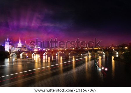 Illuminated night view of the charles bridge in prague, with twilight colors, speed lines in the czech colors and a shining light on them, from the invisible ships over the river, called vltava. - stock photo