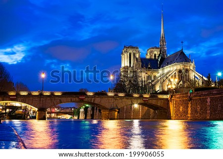 Illuminated Notre Dame Cathedral at the river Seine during twilight, Paris, France - stock photo