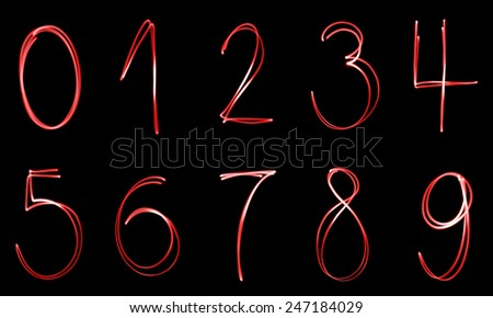 Illuminated numbers from zero in nine on a black background. - stock photo