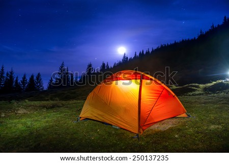 Illuminated orange camping tent under moon, stars at night  - stock photo