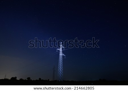 Illuminated pylon for electricity distribution at night with starry sky - stock photo