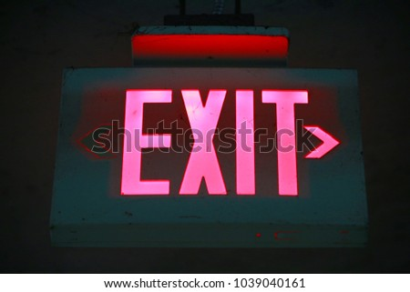 Illuminated Red Exit Sign with Arrow Pointing Right in Parking Garage at Night