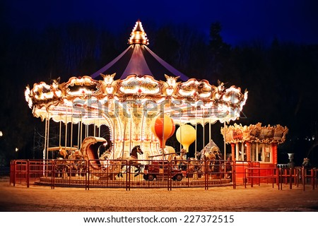 illuminated retro carousel at night - stock photo