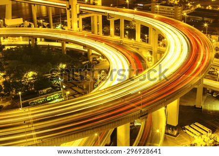 illuminated road intersection and traffic trails - stock photo