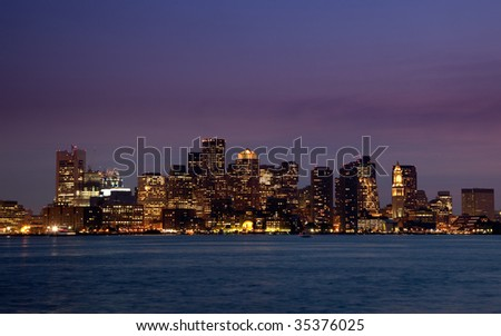 Illuminated skyscrapers of Boston at night, reflected in the water of the Charles River - stock photo