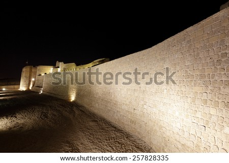 Illuminated Southern wall with moat of Bahrain Fort - stock photo