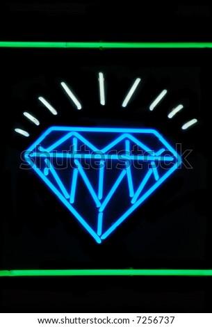 Illuminated sparkling diamond neon sign on black - stock photo