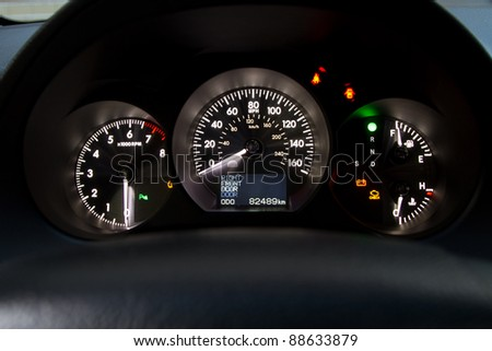 Illuminated sports car dashboard closeup photo - stock photo