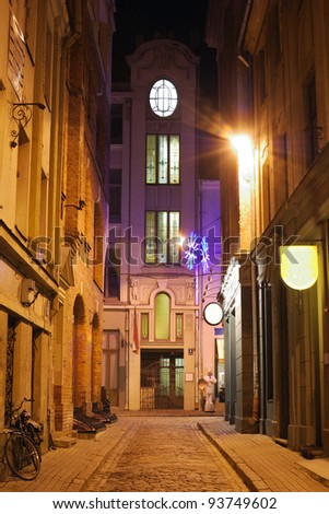 illuminated street in old part of Riga by night - stock photo