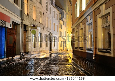 Illuminated street in old part of Riga by night in the rain