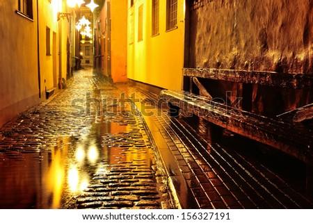 Illuminated street in old part of Riga by night in the rain - stock photo