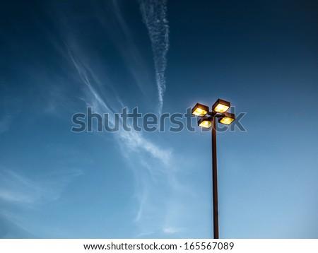 Illuminated street light lamp post against blue sky background - stock photo