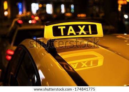 illuminated taxi sign on a taxi roof at night
