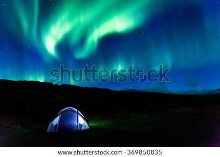 Illuminated tent and aurora in Iceland - stock photo